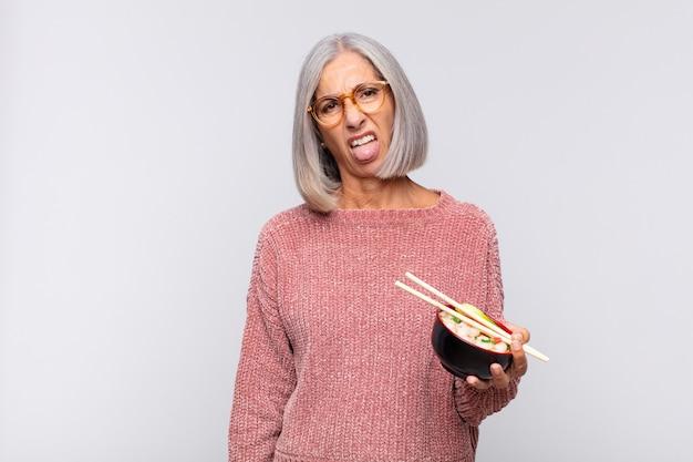 Femme d'âge moyen se sentant dégoûtée et irritée, collant la langue isolée