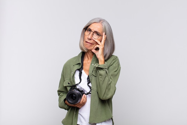 Femme d'âge moyen se sentant ennuyée, frustrée et somnolente après une tâche fatigante, terne et fastidieuse, tenant le visage avec la main. concept de photographe