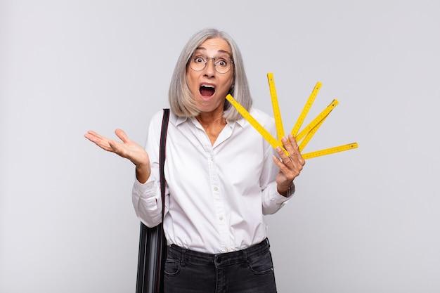 Femme d'âge moyen se sentant extrêmement choquée et surprise, anxieuse et paniquée, avec un regard stressé et horrifié. concept d'architecte