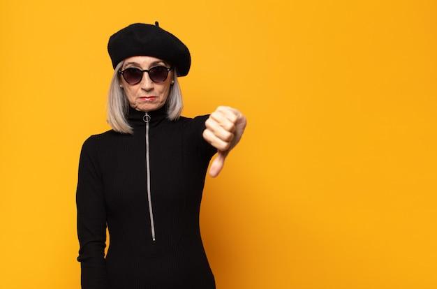 Femme d'âge moyen se sentant fâchée, en colère, agacée, déçue ou mécontente, montrant les pouces vers le bas avec un regard sérieux
