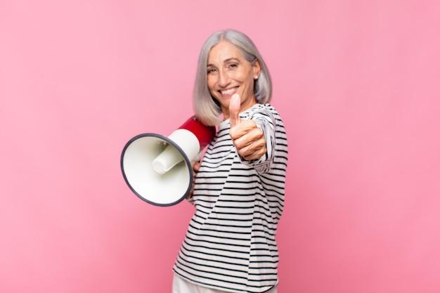 Femme d'âge moyen se sentant fière, insouciante, confiante et heureuse, souriant positivement avec le pouce levé avec un mégaphone