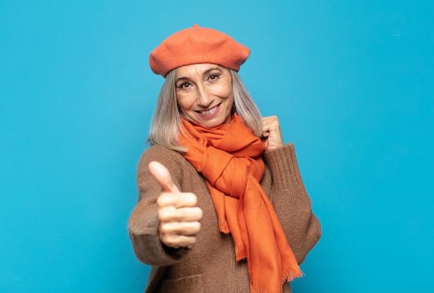 Femme d'âge moyen se sentant fière, insouciante, confiante et heureuse, souriant positivement avec le pouce levé