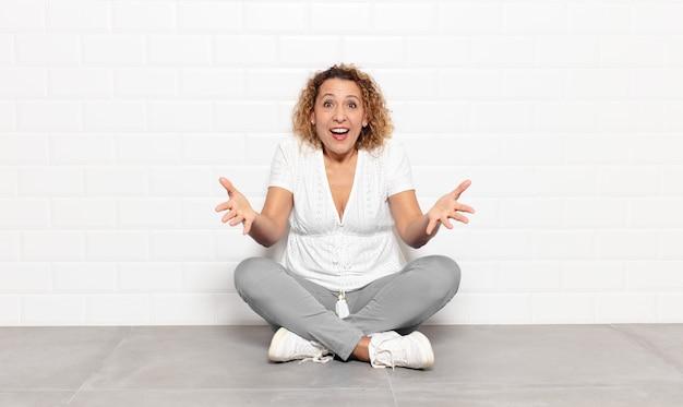 Femme d'âge moyen se sentant heureuse, étonnée, chanceuse et surprise, comme dire omg sérieusement? incroyable