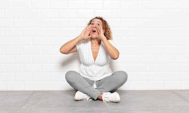 Femme d'âge moyen se sentant heureuse, excitée et positive, donnant un grand cri avec les mains à côté de la bouche, appelant