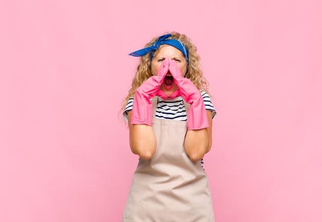 Femme d'âge moyen se sentant heureuse, excitée et positive, donnant un grand cri avec les mains à côté de la bouche