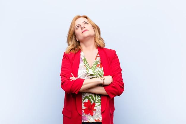Femme d'âge moyen se sentant heureuse, fière et pleine d'espoir, se demandant ou pensant, levant les yeux pour copier l'espace avec les bras croisés