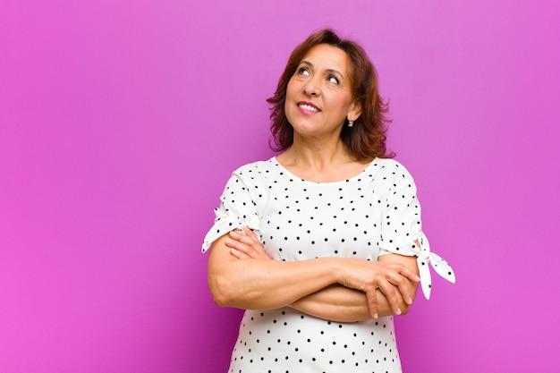 Femme d'âge moyen se sentant heureuse, fière et pleine d'espoir, se demandant ou pensant, levant les yeux