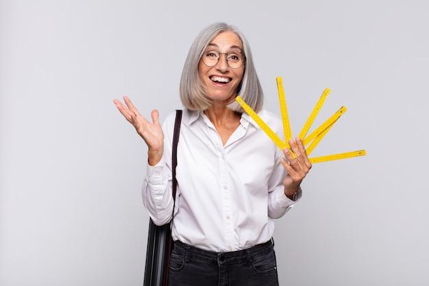 Femme d'âge moyen se sentant heureuse, surprise et joyeuse isolée