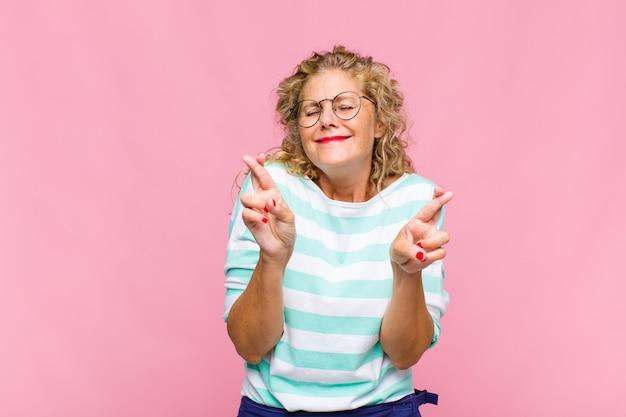 Femme d'âge moyen se sentant nerveuse et pleine d'espoir, croisant les doigts, priant et espérant avoir de la chance