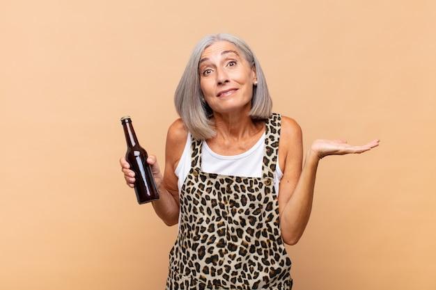 Femme d'âge moyen se sentant perplexe et confus, doutant, pesant ou choisissant différentes options avec une drôle d'expression avec une bière
