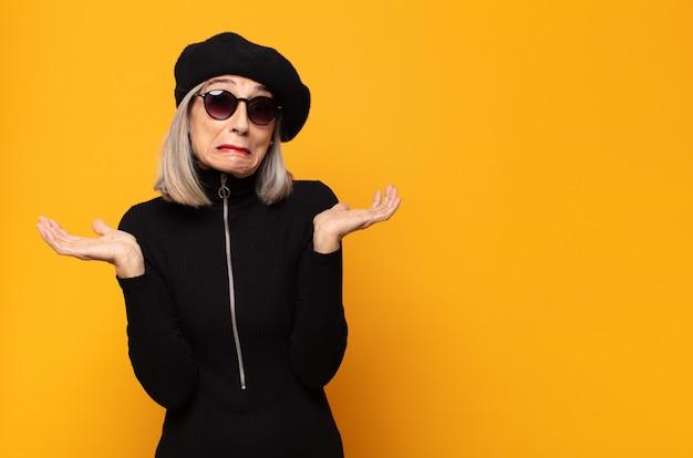 Femme d'âge moyen se sentant perplexe et confuse, doutant, pondérant ou choisissant différentes options avec une expression amusante