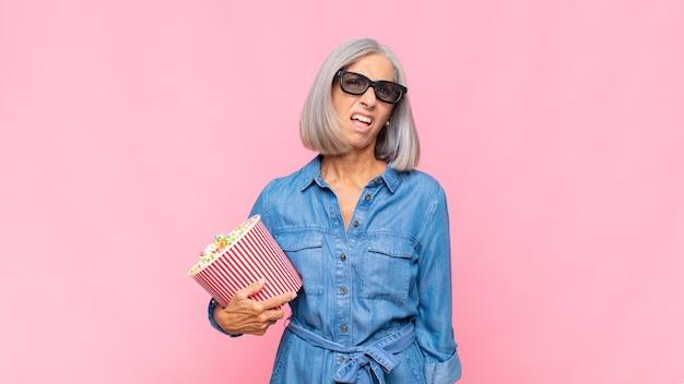 Femme d'âge moyen se sentant perplexe et confuse, avec une expression stupide et stupéfaite en regardant quelque chose de concept de film inattendu