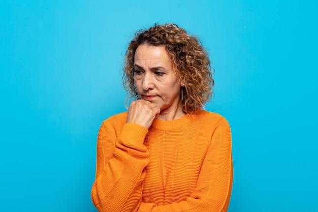 Femme d'âge moyen se sentant sérieuse, réfléchie et concernée, regardant de côté avec la main appuyée contre le menton