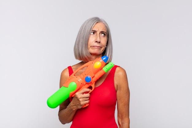 Femme d'âge moyen se sentant triste, bouleversée ou en colère et regardant sur le côté avec une attitude négative, fronçant les sourcils en désaccord avec un pistolet à eau