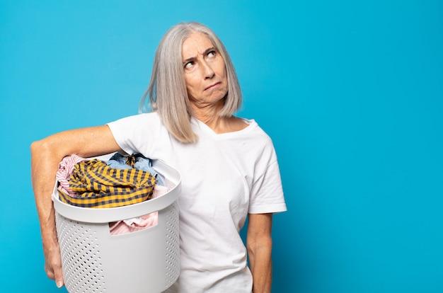 Femme d'âge moyen se sentant triste, bouleversée ou en colère et regardant sur le côté avec une attitude négative, fronçant les sourcils en désaccord