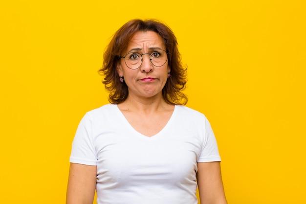 Femme d'âge moyen se sentant triste et stressée, bouleversée par une mauvaise surprise, avec un regard négatif et anxieux contre le mur jaune