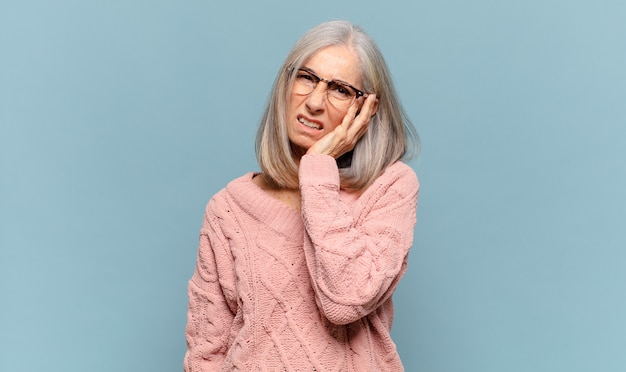 Femme d'âge moyen se sentir ennuyé, frustré et somnolent après une tâche ennuyeuse, ennuyeuse et ennuyeuse, tenant le visage avec la main