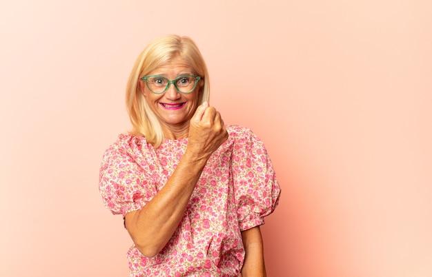 Femme d'âge moyen se sentir heureux et souriant avec désinvolture, à la recherche d'un objet ou d'un concept tenu sur la main sur le côté