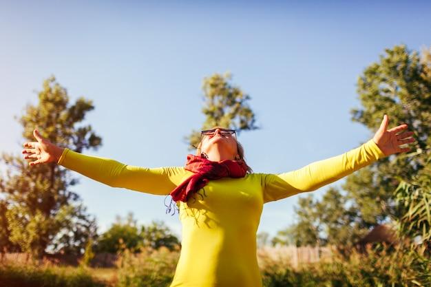 Femme d'âge moyen se sentir libre et heureuse senior dame levant les mains
