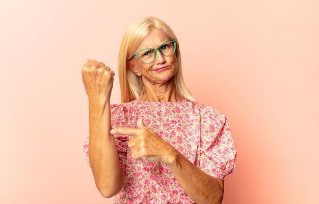 Femme d'âge moyen à la somnolence, s'ennuie et bâillements, avec un mal de tête et une main couvrant la moitié du visage