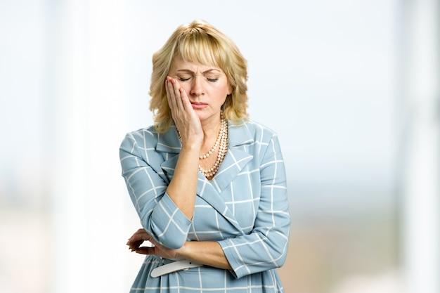 Femme d'âge moyen souffrant de maux de dents. jolie femme mature triste souffrant de fortes douleurs dentaires fermées les yeux et toucher la joue.