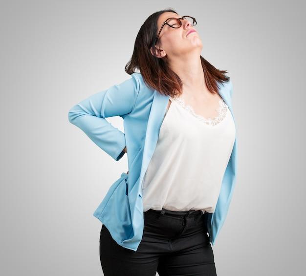 Femme d'âge moyen souffrant de maux de dos dus au stress au travail, fatiguée et astucieuse