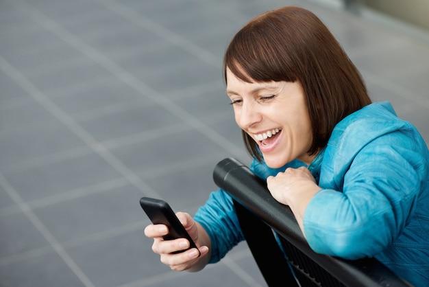 Femme d'âge moyen souriant au téléphone mobile
