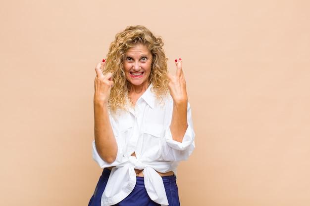 Femme d'âge moyen souriant et croisant anxieusement les deux doigts, se sentant inquiète et souhaitant ou espérant avoir de la chance