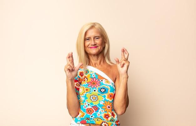 Femme d'âge moyen souriant et croisant anxieusement les deux doigts