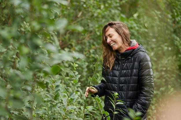 Femme d'âge moyen souriant dans la brousse tout en caressant les feuilles des arbres en hiver. cheveux blonds caucasiens