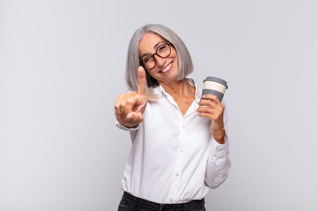 Femme d'âge moyen souriant fièrement et avec confiance en faisant le numéro un pose triomphalement, se sentant comme un concept de café leader