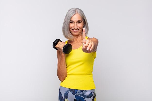 Femme d'âge moyen souriant fièrement et avec confiance en faisant la pose numéro un triomphalement, se sentant comme un leader. concept de remise en forme