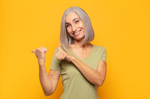 Femme d'âge moyen souriant joyeusement et désinvolte pointant vers l'espace de copie sur le côté, se sentant heureuse et satisfaite