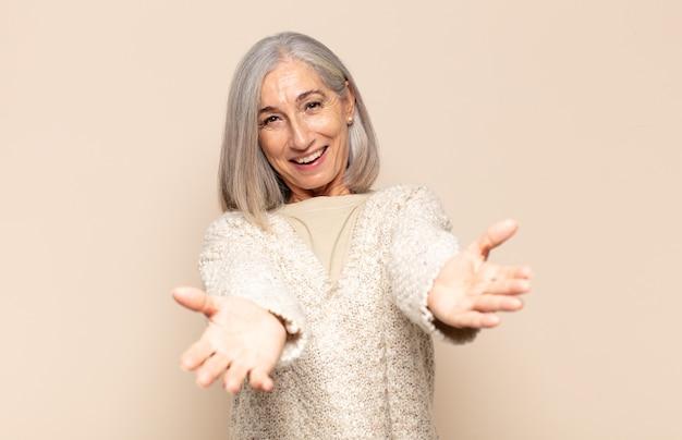 Femme d'âge moyen souriant joyeusement donnant un câlin de bienvenue chaleureux, amical et affectueux, se sentant heureuse et adorable