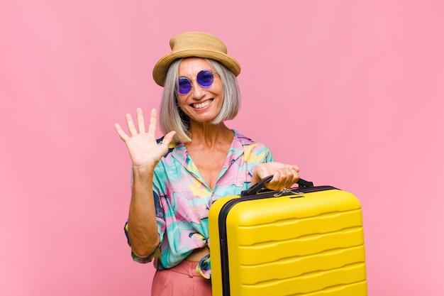 Femme d'âge moyen souriant joyeusement et gaiement, en agitant la main, en vous accueillant et en vous saluant, ou en vous disant au revoir