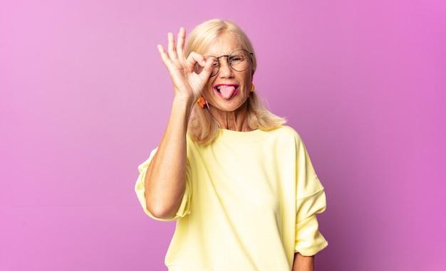 Femme d'âge moyen souriant joyeusement avec grimace, plaisantant et regardant à travers le judas, espionnant les secrets