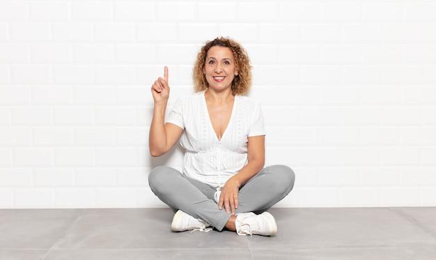 Femme d'âge moyen souriant joyeusement et joyeusement, pointant vers le haut d'une main pour copier l'espace