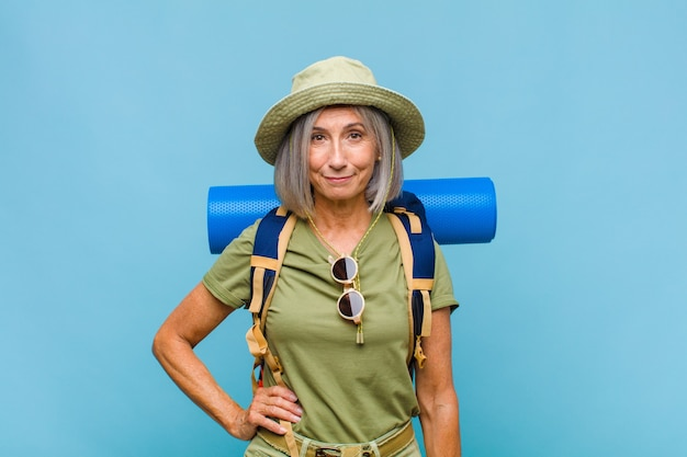 Femme d'âge moyen souriant joyeusement avec une main sur la hanche et une attitude confiante, positive, fière et amicale