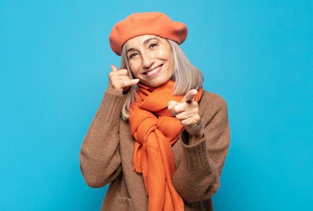Femme d'âge moyen souriant joyeusement et pointant tout en faisant un appel, vous geste plus tard, parler au téléphone