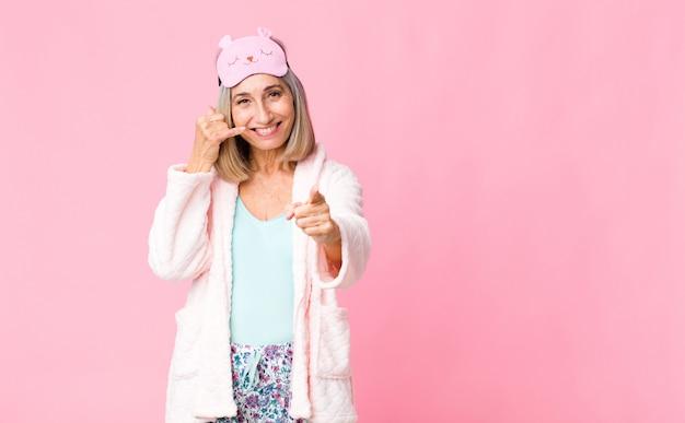 Femme d'âge moyen souriant joyeusement et pointant tout en vous appelant plus tard, en parlant au téléphone. concept de costume de nuit