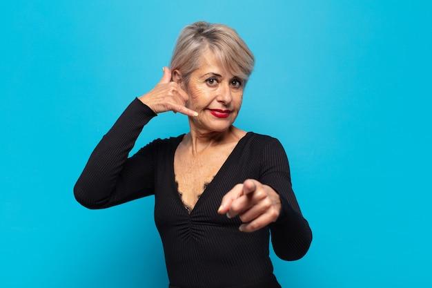 Femme d'âge moyen souriant joyeusement et pointant vers la caméra tout en faisant un appel, vous geste plus tard, parler au téléphone