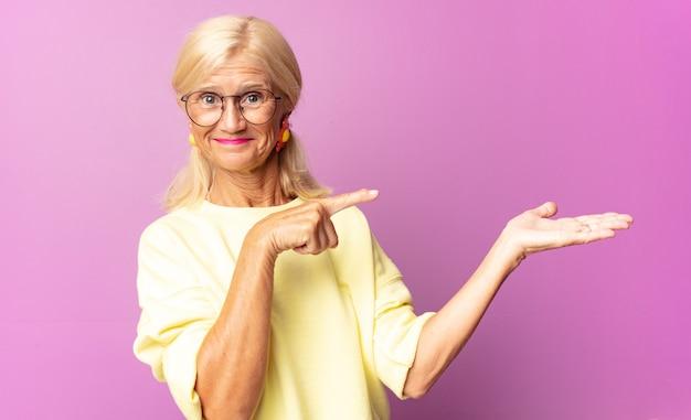 Femme d'âge moyen souriant joyeusement et pointant vers l'espace de copie sur la paume sur le côté, montrant ou annonçant un objet