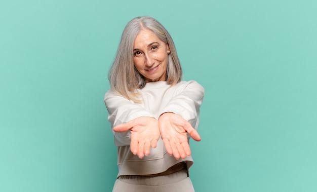 Femme d'âge moyen souriant joyeusement avec un regard amical, confiant et positif, offrant et montrant un objet ou un concept