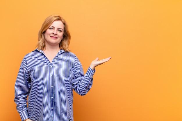 Femme d'âge moyen souriant joyeusement, se sentant heureux et montrant un concept dans l'espace de copie avec la paume de la main