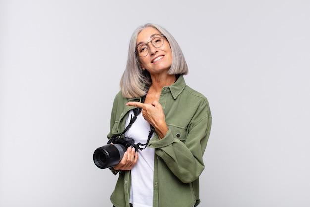 Femme d'âge moyen souriant joyeusement, se sentant heureux et pointant isolé