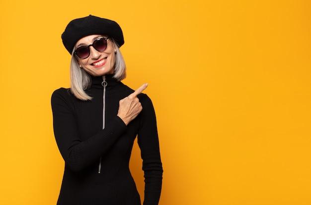 Femme d'âge moyen souriant joyeusement, se sentant heureux et pointant vers le côté et vers le haut, montrant l'objet dans l'espace de copie