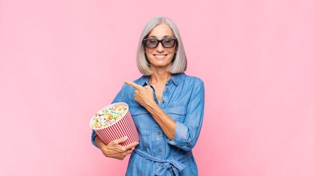 Femme d'âge moyen souriant joyeusement, se sentant heureux et pointant