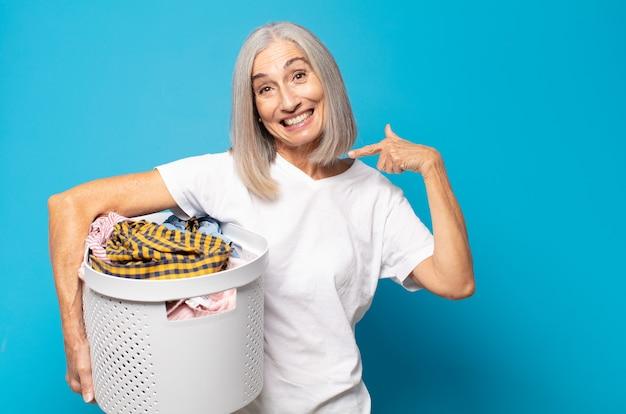 Femme d'âge moyen souriant pointant avec confiance vers son large sourire, attitude positive, détendue et satisfaite