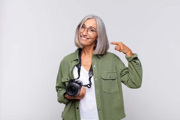 Femme d'âge moyen souriant pointant avec confiance vers son large sourire