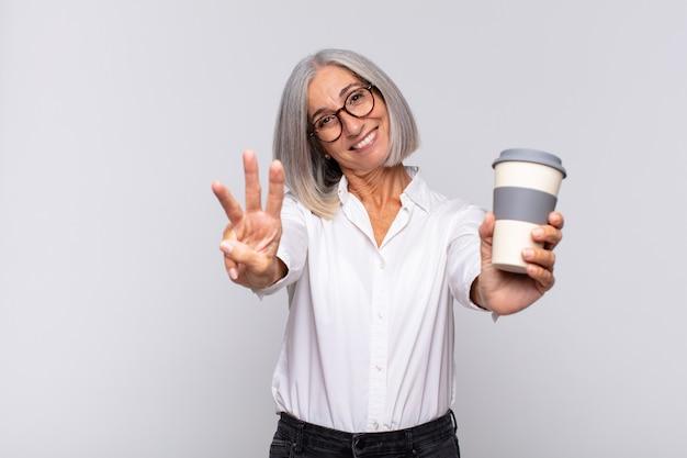 Femme d'âge moyen souriant et à la recherche amicale, montrant le numéro trois ou troisième avec la main vers l'avant, compte à rebours du concept de café